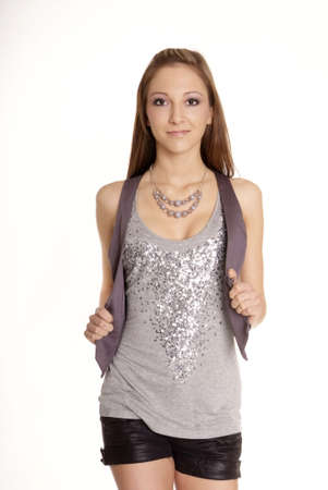 nice young woman with long hair in pants and silver top standing Stock Photo