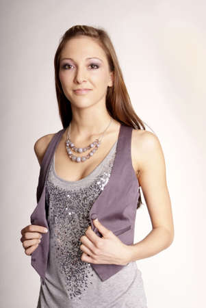friendly young woman with long brunette hair and silver sequined shirt