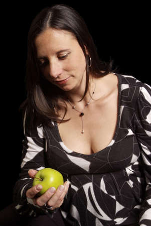 pregnant woman hold green apple in hand