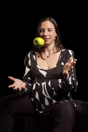 pregnant woman throw green apple up in air