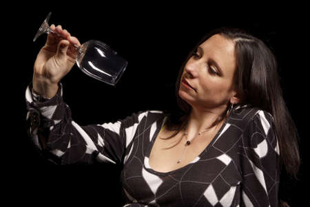 adult woman looks serious at empty wine glass