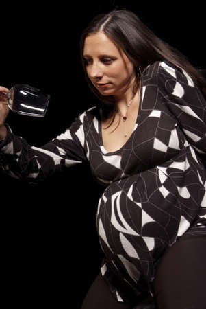 pregnant woman looks serious at empty wine glass