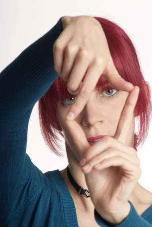 young woman holding fingers like frame in front of face