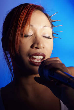 womanhood: young woman singing with passion in microphone