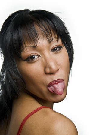 audacious: portrait of a young pretty asian woman stick her tongue out