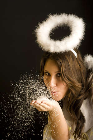 young woman with nimbus blow snow off hand