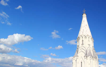 godly: The white tower of church on background of blue sky