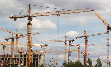 concrete commercial block: Construction cranes at a construction site on a working day