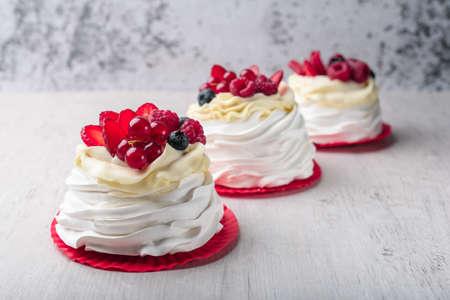 Pavlova meringue cake with cream and raspberries, blueberries, strawberries, currants