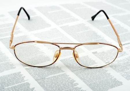 opthalmology: Eyeglasses golden on text background.