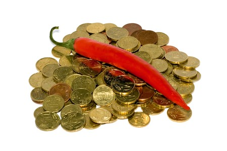 Heap of coins and red hot chili peppers isolated on white background Stock Photo