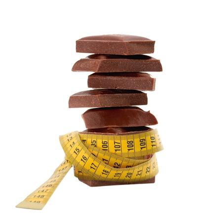 chocolade blokken in meetlint, Dieet concept, geïsoleerd op een witte achtergrond Stockfoto