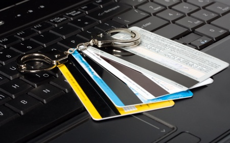 credit card of handcuffs on a computer keyboard Stock Photo - 13116215