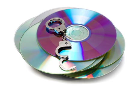 gigabytes: handcuffs on stack of Cd or DVD roms isolated on white background