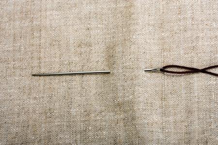Nadel und Faden auf den Hintergrund Stoffen