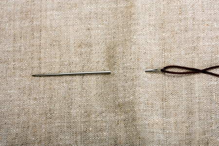 needle and thread on background fabrics