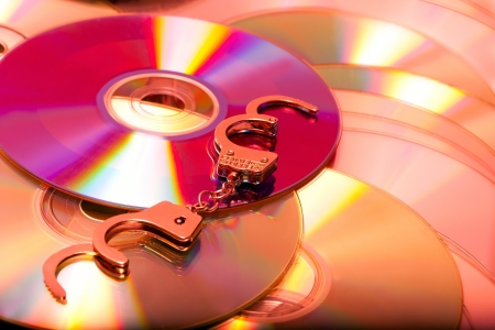 handcuffs in pile pirate dvd computer disc Stock Photo