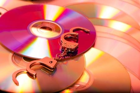 warez: handcuffs in pile pirate dvd computer disc Stock Photo