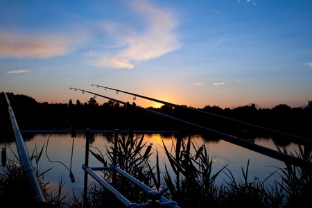 fishing scene: carp fishing sunrise - spinning on rod pod