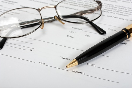 Signing contract-glasses and gold pen   photo
