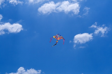 The kite flying colors against the blue sky photo