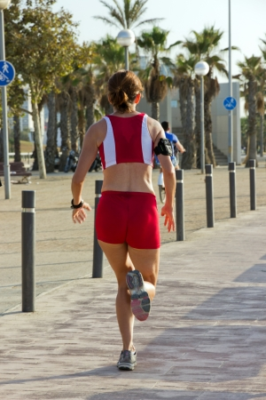 Back view of a girl running on road  Morning jog  photo