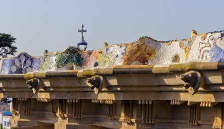 cross and mosaic bench on stone gallery in the park Guell in Barcelona - Spain