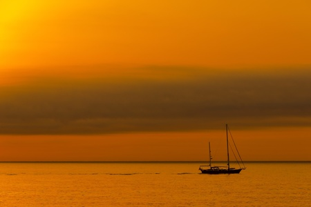 Dawn sailboat silhouette on ocean photo