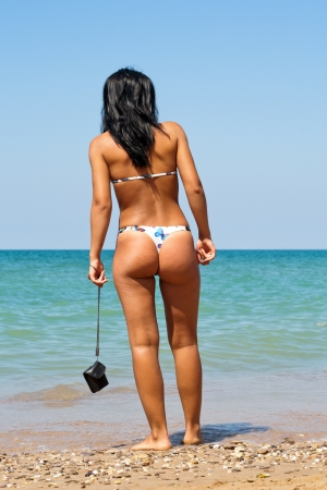beautiful woman in bikini standing looking view of beach sea   photo
