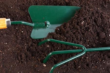 gardening tools shovel rake on peat background  Reklamní fotografie