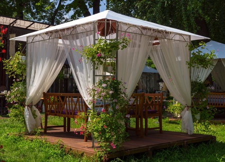 white wedding or entertainment tent in flowering garden 스톡 콘텐츠