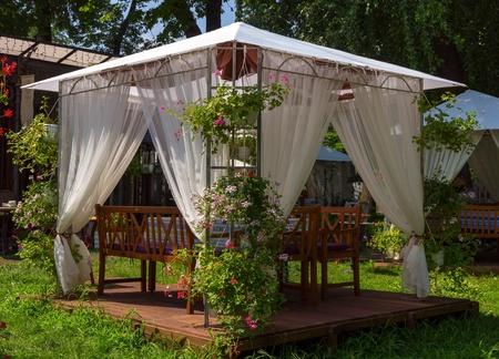 white wedding or entertainment tent in flowering garden Stock Photo