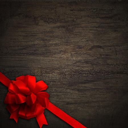 Red bow on black wall wood texture background photo