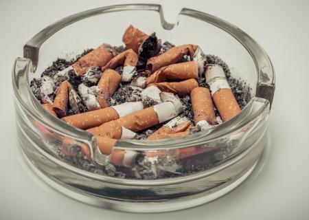 enfermedades del corazon: Colillas de cigarrillo en un cenicero de cristal de fondo estilo retro de la vendimia. Foto de archivo