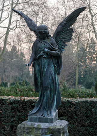 Sculpture of ancient Angel on vintage tombstone photo