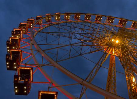 carrousel: Ferris whiil of illuminatedl in city park. Stock Photo