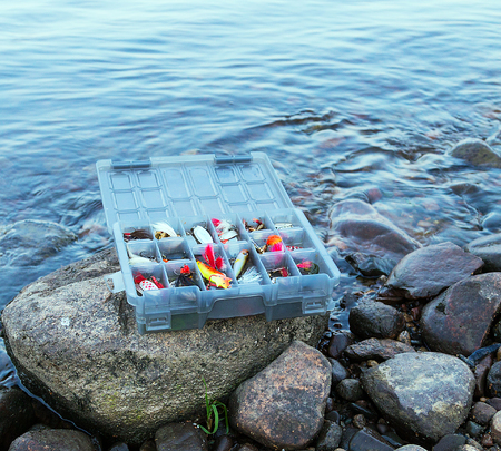 Colorful fishing fish lures in a box in coast river photo