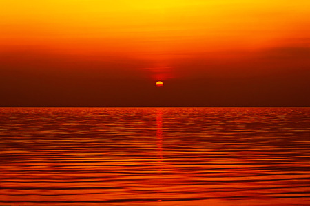 gold sun setting over the sea  photo