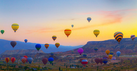 sunset Hot air balloons landing in a mountain Cappadocia Goreme National Park Turkey.