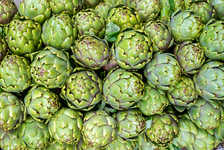 Background of fresh artichokes for sale at a farmers' market