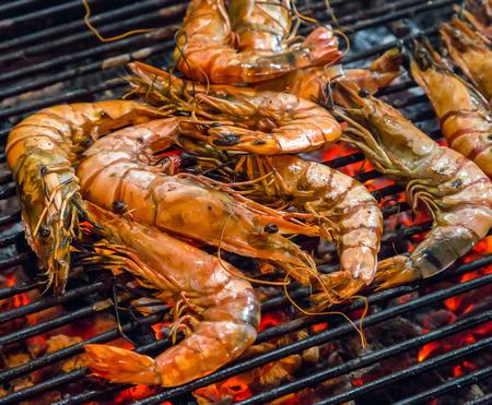 Gebakken koning garnalen zeevruchten door vuur en BBQ Flames. Restaurant Barbecue bij de avondmarkt Stockfoto