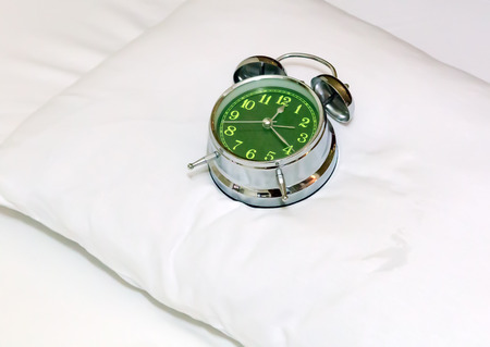 wakening: Alarm clock on bed sheets background