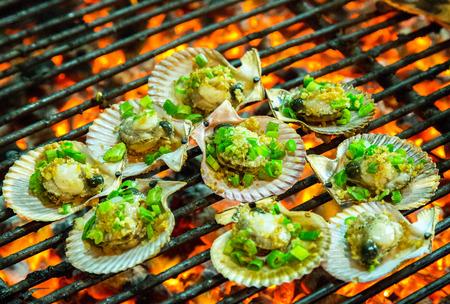 ostra: Asar a la parrilla ostras alimentos en la parrilla en llamas. Verano concepto de barbacoa de mariscos.