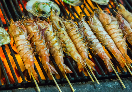 prepared shrimp, prawn grilled barbecued mixed seafood in BBQ Flames.