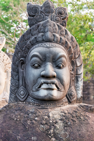 woodland sculpture: head daemon of Angkor Wat, part of Khmer temple complex, Asia. Siem Reap, Cambodia. Ancient Khmer architecture in jungle. Stock Photo