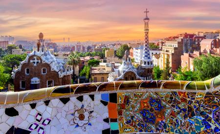 zonsopgang Parc Guell ontworpen door Antoni Gaudi gelegen aan Carmel Hill, bank bedekt met tegel-scherf mozaïek, Barcelona, Spanje. Stockfoto