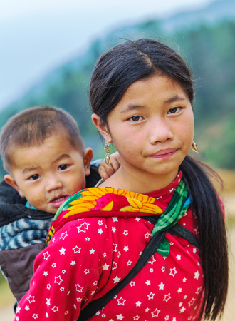 developing country: SAPA, LAO CAI, VIETNAM - NOV 21, 2014: Woman from Black Hmong Hill Tribe, children girl smile, famous tourist destination in Vietnam, Sa pa District, Lao Cai, Vietnam. Editorial