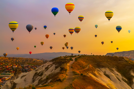 Hot air balloons landing in a mountain Cappadocia Goreme National Park Turkey.