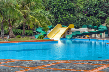 water park: outdoor swimming pool, water slide at aquapark. Summer holiday water park Editorial