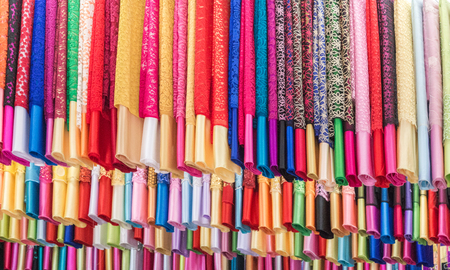 canva: Textile Cloth and tissue of various colours market, fabric and textiles in a factory shop or store or bazar.